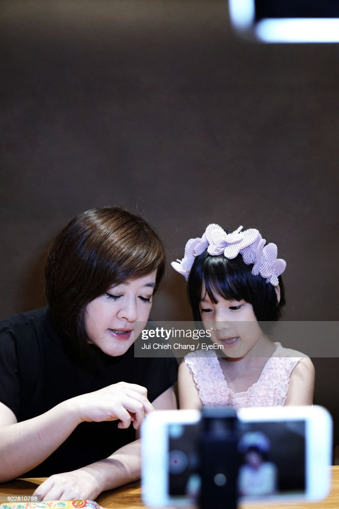 Close-Up Of Mobile Phone Photographing Woman With Daughter : Stock Photo