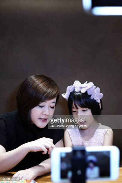 Close-Up Of Mobile Phone Photographing Woman With Daughter