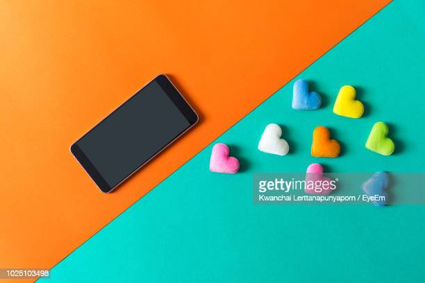 close-up of mobile phone with colorful heart shapes over colored background - long distance relationship stock pictures, royalty-free photos & images