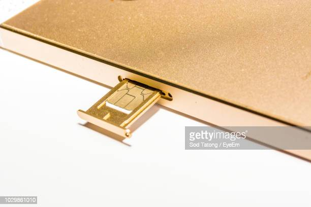 Close-Up Of Mobile Phone With Sim Card On White Background