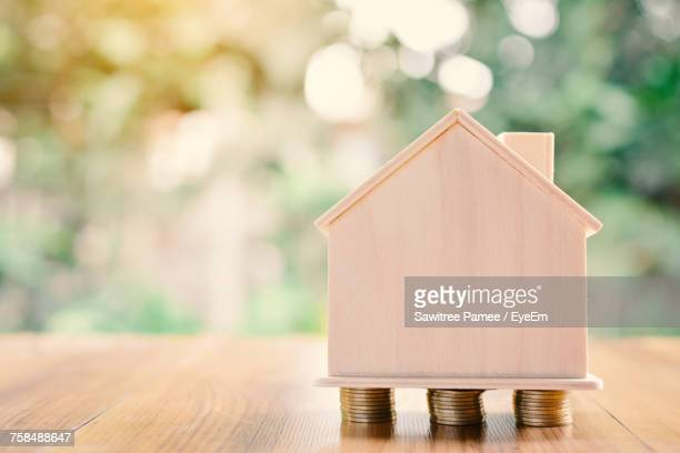 Close-Up Of Model House On Coins Over Table