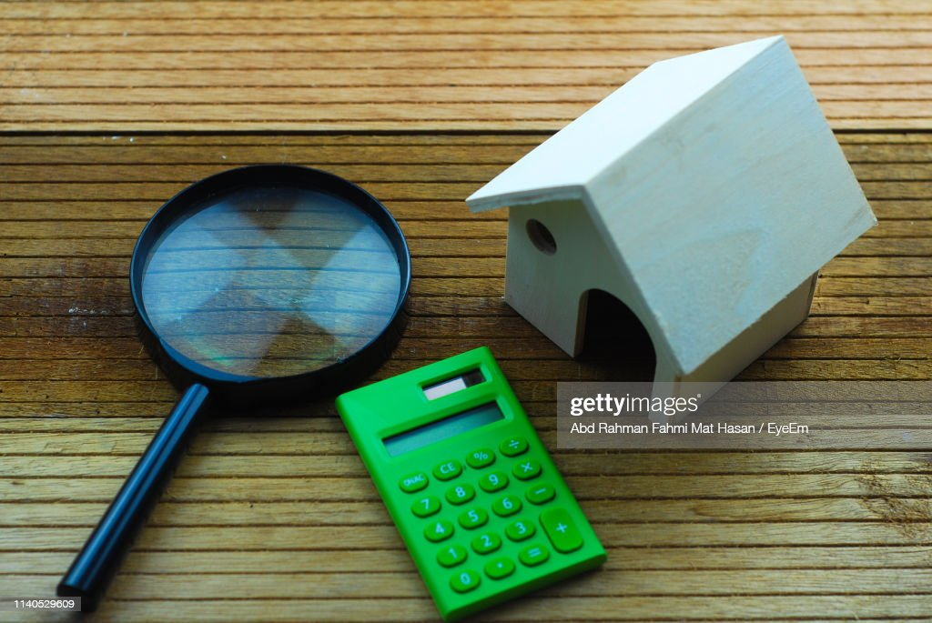 Close-Up Of Model House With Magnifying Glass And Calculator On Table : Stock Photo