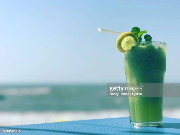 close-up of mojito on table against sea - nancy green stock pictures, royalty-free photos & images