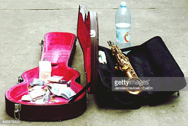 Close-Up Of Money In Guitar Case With Trumpet Beside It