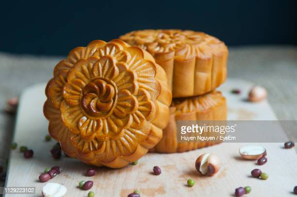 close-up of moon cakes with seeds on cutting board - moon cake stock pictures, royalty-free photos & images