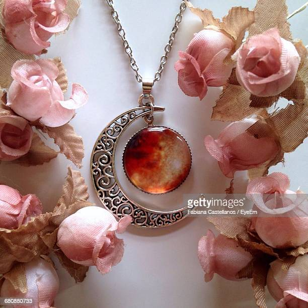 close-up of moon shape pendent amidst roses on table - necklace stock pictures, royalty-free photos & images