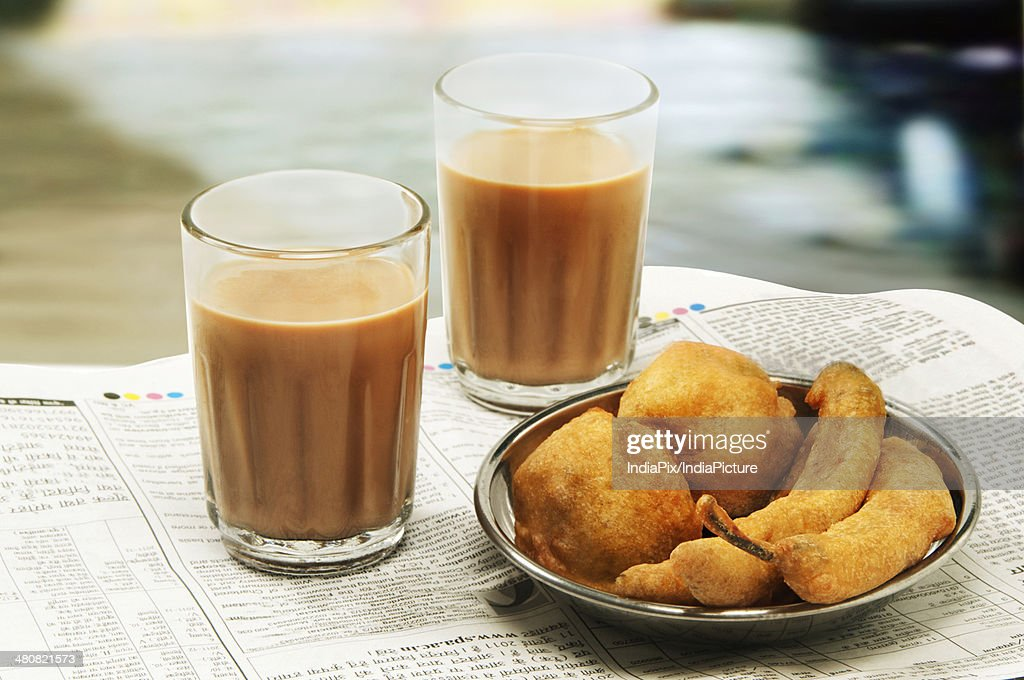 Close-up of morning chai with bhajiyas and vada on newspaper : Stock Photo