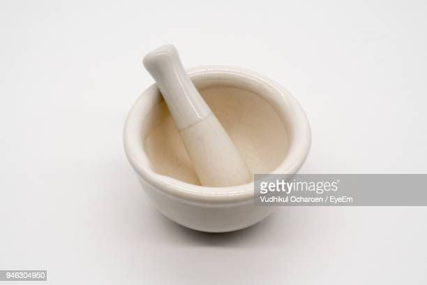 Close-Up Of Mortar And Pestle Against White Background