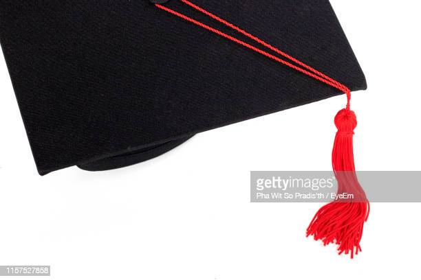close-up of mortarboard against white background - tassel stock pictures, royalty-free photos & images