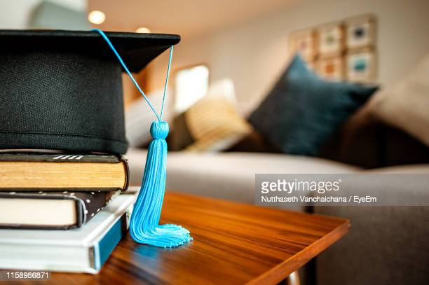 close-up of mortarboard and books on table at home - graduation stock pictures, royalty-free photos & images