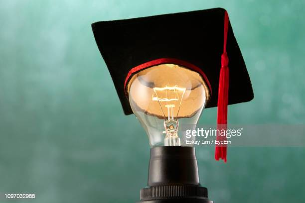 close-up of mortarboard on illuminated light bulb against blue background - graduation background stock pictures, royalty-free photos & images