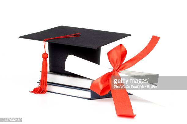 close-up of mortarboard with certificate and books against white background - graduation background stock pictures, royalty-free photos & images