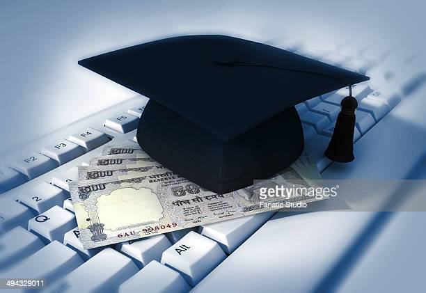 close-up of mortarboard with indian currency on keyboard representing software graduation - stipendium stock-fotos und bilder