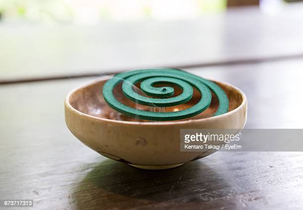 Close-Up Of Mosquito Coil In Bowl On Wooden Table