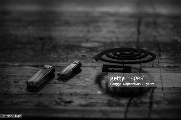 close-up of mosquito coil with cigarette lighter on table - incense coils stock pictures, royalty-free photos & images