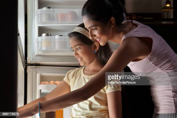 Close-up of mother and daughter keeping food in refrigerator at night