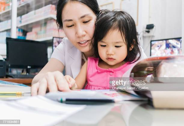 close-up of mother and daughter sitting indoors - chanayut stock photos and pictures