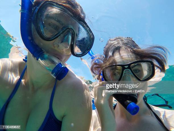 close-up of mother and daughter snorkeling undersea - lady barbara stock-fotos und bilder
