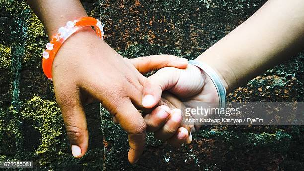 Close-Up Of Mother And Girl Holding Hands