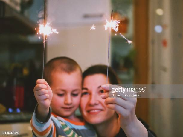 close-up of mother and son playing with burning sparklers - daniel funke stock-fotos und bilder