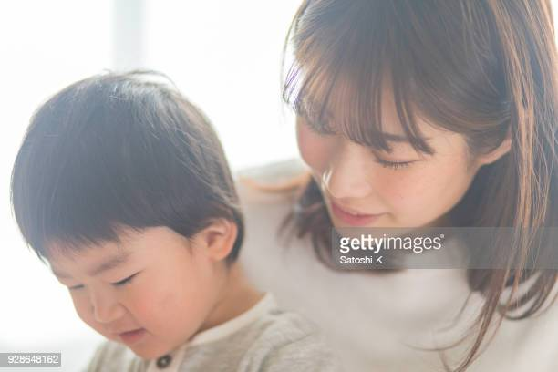 close-up of mother and son reading book together - only japanese stock pictures, royalty-free photos & images