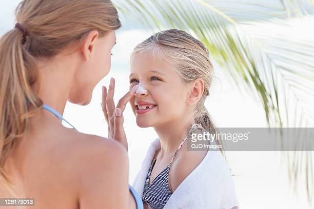 close-up of mother applying suntan lotion on daughter's nose - lotion stock photos and pictures