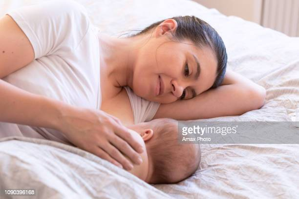close-up of mother breastfeeding and hugging newborn baby. mom breast feeding her infant baby. lactation newborn concept. baby eating milk before sleeping. mother feed her month son with breast milk - breastfeeding stock pictures, royalty-free photos & images