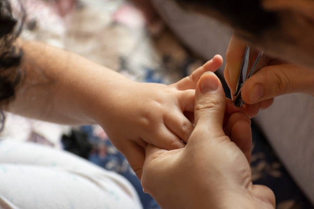 close-up of mother cutting nails of daughter - trim nail for children stock pictures, royalty-free photos & images