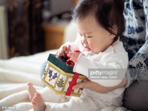 close-up of mother helping daughter in unwrapping christmas gift - 1歳以上2歳未満 ストックフォトと画像