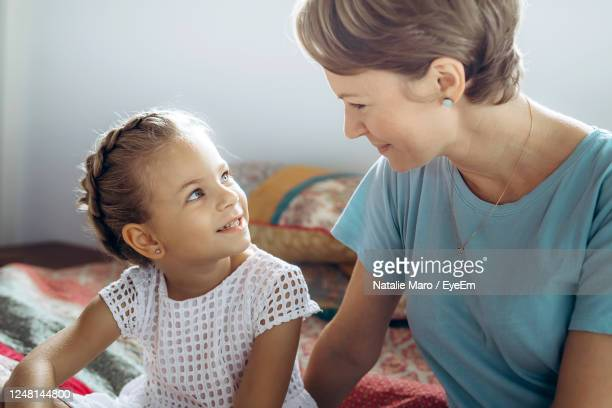 close-up of mother talking with daughter sitting on bed at home - child in bed clothed stock pictures, royalty-free photos & images