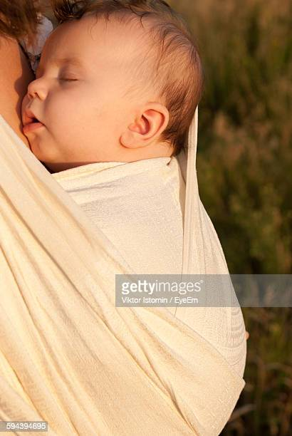 Close-Up Of Mother With Baby Carrying In Fabric