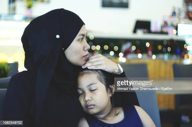 Close-Up Of Mother With Sleeping Daughter Sitting At Restaurant