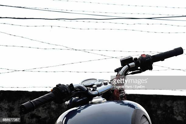 Close-Up Of Motorcycle By Barbed Wire Fence Against Sky