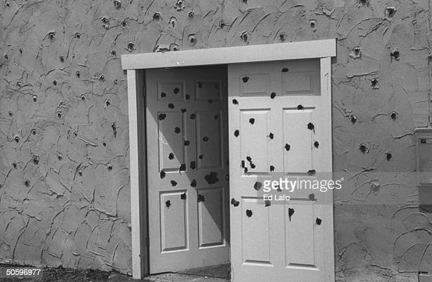 Closeup of movie set replica of Davidian compound doorway & walls riddled w. Bullet holes from ATF agents attack, during break in filming TV movie In...