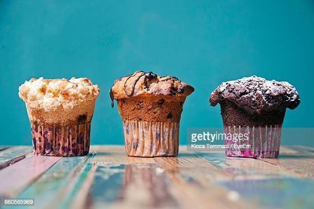 close-up of muffins on table against wall - muffin stock pictures, royalty-free photos & images