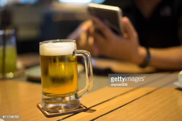 Close-up of mug and cups with beer glass out by business man using smart-phone after work
