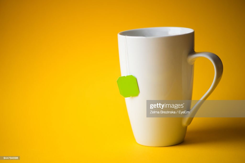 Close-Up Of Mug With Tea Bag Against Yellow Background : Stock Photo
