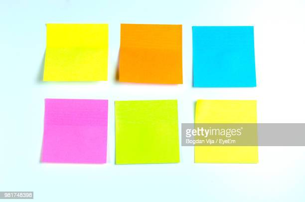 close-up of multi colored adhesive notes against white background - adhesive note stock pictures, royalty-free photos & images