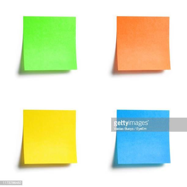 close-up of multi colored adhesive notes on white background - adhesive note stock pictures, royalty-free photos & images