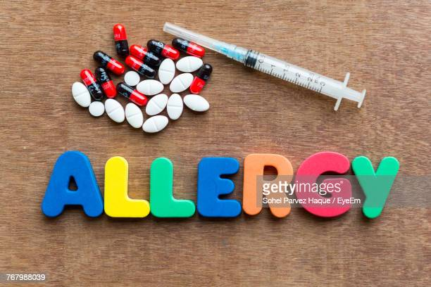 Close-Up Of Multi Colored Allergy Text With Pills And Syringe On Table