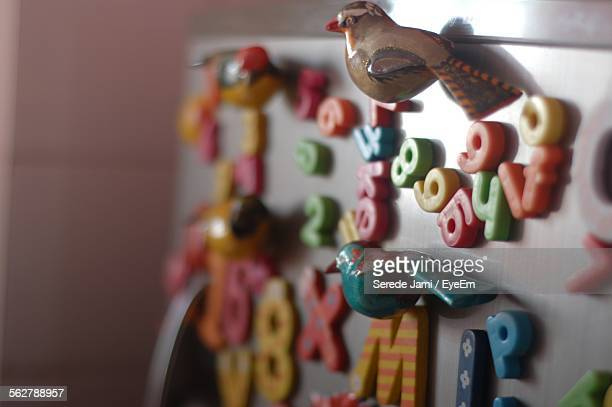 Close-Up Of Multi Colored Alphabets With Artificial Birds Stuck On Fridge
