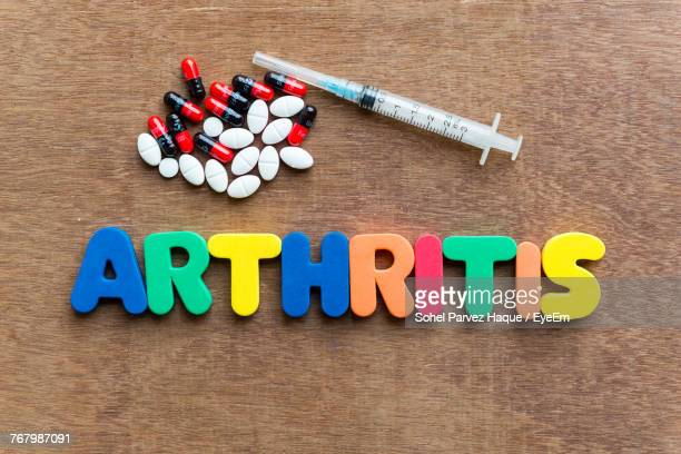 Close-Up Of Multi Colored Arthritis Text With Pills And Syringe On Table