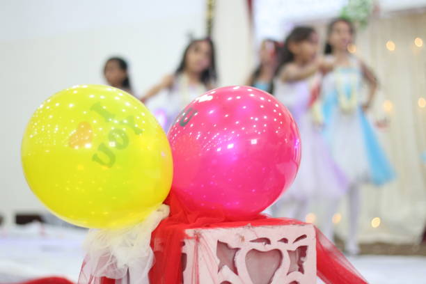 Close-Up Of Multi Colored Balloons With Girls In Background