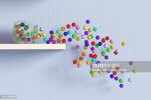 Close-Up Of Multi Colored Balls Falling From Glass Jar Against Wall