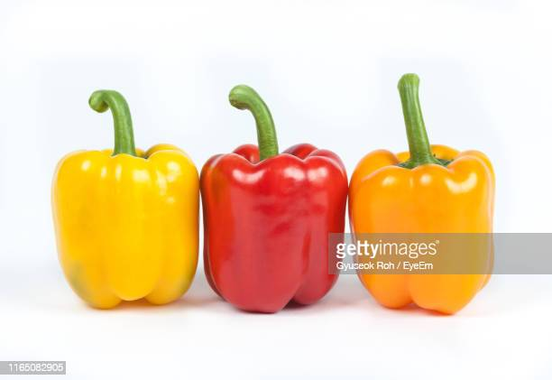 close-up of multi colored bell peppers against white background - pimiento naranja fotografías e imágenes de stock