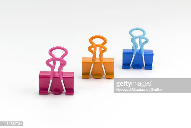 close-up of multi colored binder clips over white background - binder clip stock pictures, royalty-free photos & images