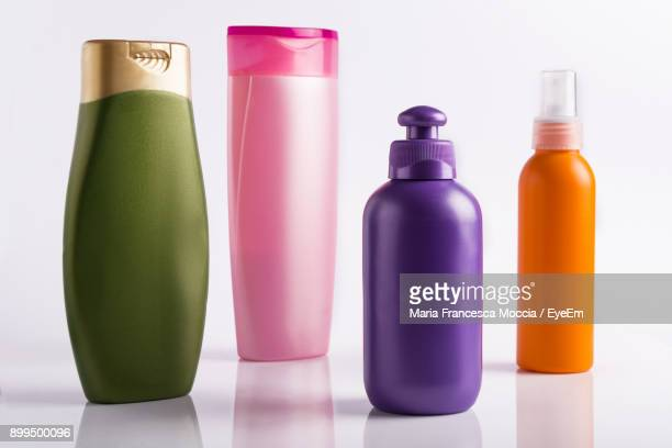 Close-Up Of Multi Colored Bottles Against White Background