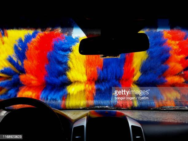 close-up of multi colored brushes seen through windshield - car wash brush stock pictures, royalty-free photos & images