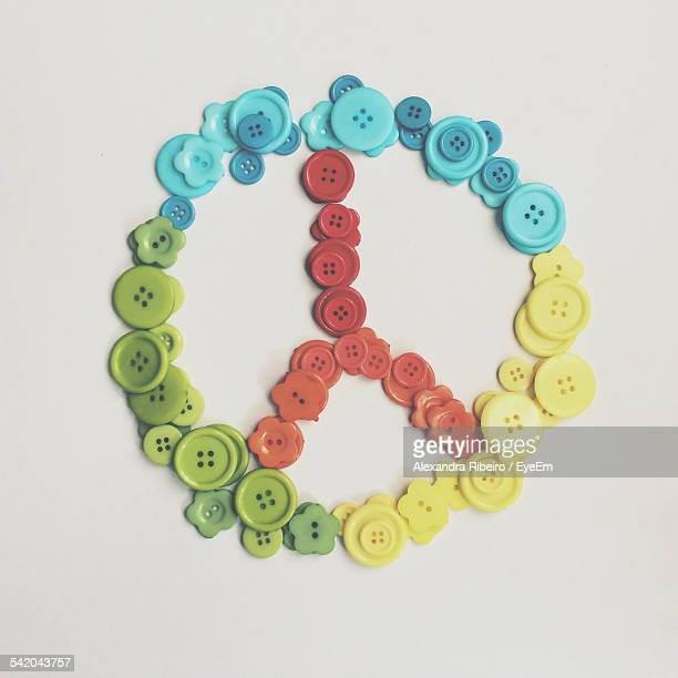 Close-Up Of Multi Colored Buttons Arranged In Peace Symbol On White Table