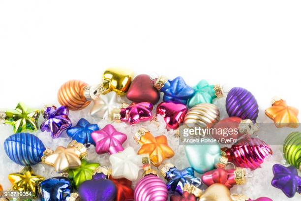 close-up of multi colored christmas ornaments against white background - angela rohde stock-fotos und bilder